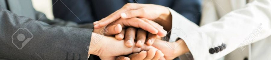 close up of multiracial business people putting their hands together, focus on hands